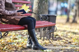 woman with book sitting on bench