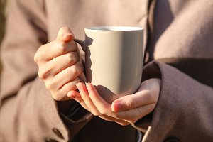 cup of coffee or tea in female hand