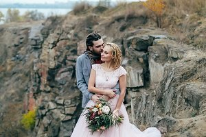 Newlyweds with hands up are embracing before a mountain cliff. Autumn wedding ceremony outdoors. Full length