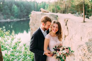 Attractive couple newlyweds bride and groom laugh and smile, happy and joyful moment. Wedding ceremony outdoors