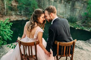 Newlyweds sitting at the edge of the canyon and couple looking each other with tenderness and love. Bride and groom touching foreheads. Wedding