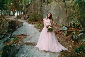 Bride with rustic wedding bouquet stands on the rock