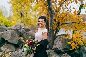 Stylish bride with a rustic bouquet is posing before a lake on the hill. Young blonde in a knitted hat with pompom and with dreadlocks. Autumn wedding ceremony outdoors.