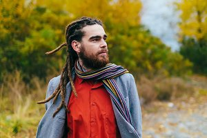 Hipster. A stylish man with dreadlocks and beard in a red shirt and grey jacket. Groom posing on nature. Autumn wedding ceremony outdoors.