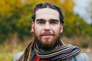 A stylish man with dreadlocks and beard in a red shirt and grey jacket. Groom posing on nature. Autumn wedding ceremony outdoors. Hipster