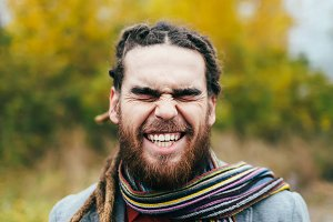 Hipster is smiling. A stylish man with dreadlocks and beard in a red shirt and grey jacket. Groom posing on nature. Autumn wedding ceremony outdoors.
