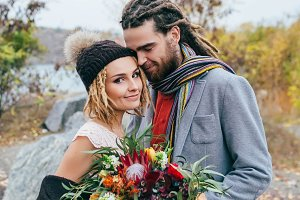 Portrait of affectionate newlyweds posing with a rustic bouquet on nature. Stylish bride in a knitted hat with pompom and groom with dreadlocks. Autumn wedding ceremony