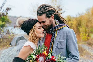 Portrait of affectionate newlyweds touching by their noses. Bride and groom posing on nature. Autumn wedding ceremony