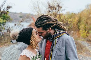 A tender moment before a kiss. Stylish bride in a knitted hat with pompom and groom with dreadlocks. Autumn wedding ceremony