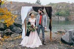 Stylish bride and groom with dreadlocks are holding hands next to wedding arch. Autumn wedding ceremony outdoors. Happy newlyweds