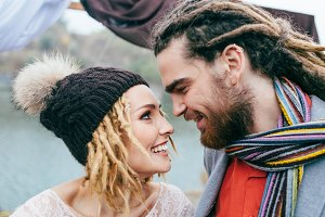 Bride in a knitted hat with pompom and groom with dreadlocks and scarf look at each other with tenderness and love. Close-up
