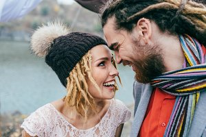 Attractive couple newlyweds laugh and smile happy and joyful moment. Autumn wedding ceremony outdoors. Stylish bride and groom with dreadlocks look at each other standing before a lake