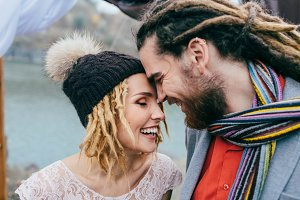 Stylish couple newlyweds smile and touching foreheads standing before a lake. Autumn wedding ceremony outdoors. Bride and groom with dreadlocks look at each other with tenderness and love