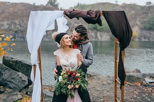 Groom tenderly embracing her beautiful bride by behind. Autumn wedding ceremony in rustic style outdoors. Happy newlyweds