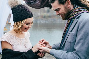 Groom puts a ring on the finger of the bride. Autumn wedding ceremony outdoors. Newlyweds with dreadlocks look at each other standing near bridal arch