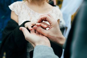 Groom puts a ring on the finger of the bride. Autumn wedding ceremony outdoors. Artwork