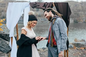 Bride is putting a wedding ring on a groom's finger, happy and joyful moment. Autumn wedding ceremony outdoors. Newlyweds with dreadlocks look at each other standing near bridal arch