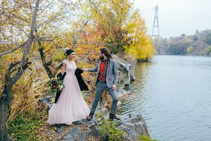 Stylish couple newlyweds walking near a lake. Bride and groom with dreadlocks are holding hands. Autumn wedding ceremony. Full length portrait