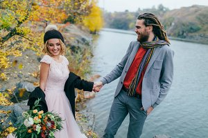 Stylish couple newlyweds walking near a lake. Bride and groom with dreadlocks are holding hands. Autumn wedding ceremony. Close-up
