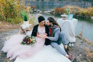 Stylish couple newlyweds are relaxing on a plaid and sitting before a lake. Bride and groom with dreadlocks are posing on nature. Autumn wedding ceremony outdoors