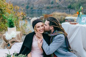 Groom tenderly kissing her beautiful bride in cheek. Autumn wedding ceremony in rustic style outdoors. Newlyweds are posing on nature backgroun