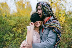 Bride in a knitted hat with a pom pom, hat covering her eyes. Groom in a colorful scarf. Wedding ceremony outdoors.