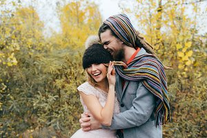 A happy couple goes crazy in. Bride in a knitted hat with a pompon and groom in colorful scarf are having fun. Wedding ceremony outdoors.
