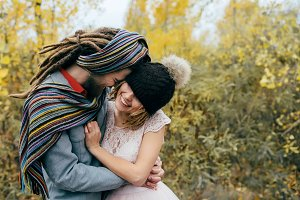 A cheerful couple goes crazy in. Bride in a knitted hat with a pompon and groom in colorful scarf are having fun. Wedding ceremony outdoors.