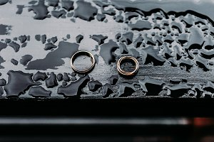 Wedding rings on a dark wooden background with drops of water. Unusual Jewelry Photo