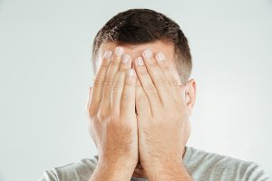 Man covering face with hands.