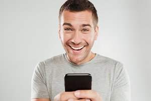 Happy man using mobile phone chatting.