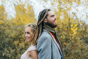 A cheerful couple stands back to back. Bride and groom with dreadlocks having fun on nature. Wedding ceremony outdoors.