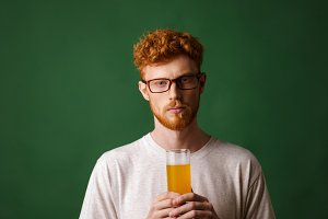Portrait of a young redhead man holding glass of beer