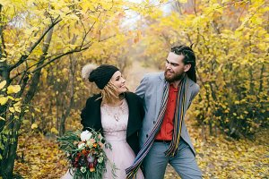 A happy couple is walking on a trail in an autumn forest. Bride and groom with dreadlocks are looking at each other on nature. Wedding ceremony outdoors.