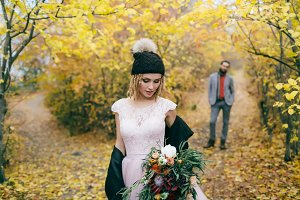 Beautiful bride in a knitted hat with a pompon are posing in autumn forest on blurred groom's background. Wedding ceremony outdoors.