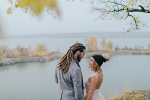 Attractive couple newlyweds laugh and smile. Autumn wedding ceremony outdoors. Stylish bride and groom with dreadlocks look at each other standing before a lake.