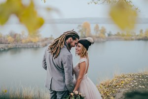 Stylish couple newlyweds smile and touching foreheads standing before a lake. Bride and groom with dreadlocks look at each other standing before a lake. Autumn wedding ceremony outdoors.