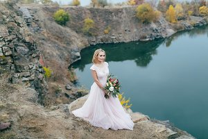 Stylish bride with a rustic bouquet is posing before a lake on the hill. Autumn wedding ceremony outdoors. Full length