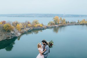 Stylish couple newlyweds smile and hugging standing before a lake. Bride and groom with dreadlocks look at each other. Autumn wedding ceremony outdoors.