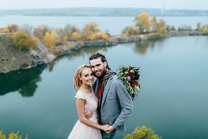 Stylish couple newlyweds are posing before a lake on the hill. Autumn wedding ceremony outdoors. Close-up