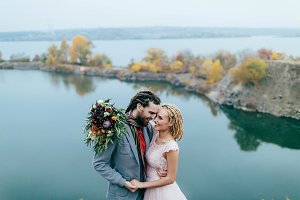 Stylish couple newlyweds smile and hugging standing before a lake. Bride and groom with dreadlocks look at each other. Autumn wedding ceremony outdoors. Close-up