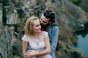 Stylish couple newlyweds posing on mountains background. Bride and groom with dreadlocks are hugging. Autumn wedding ceremony.