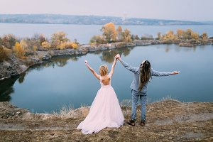 Back view of stylish couple newlyweds with hands up are posing before a lake on the hill. Autumn wedding ceremony outdoors. Full length