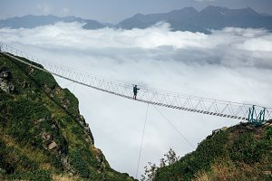 Man standing in the middle of suspension bridge and looking at cloudy mountains below.