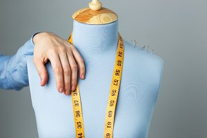 Fashion designer and blue tailor dummy with measuring tape close up photo.