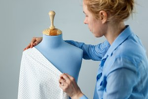 Seamstress measuring beautiful fabric on blue tailor dummy in her workshop.