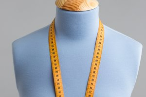 Blue tailor dummy with measuring tape alongside the wall.