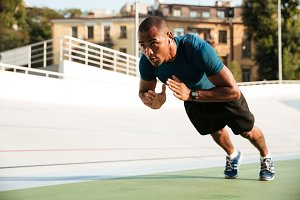 Portrait of a fit afro american sportsman doing push-ups