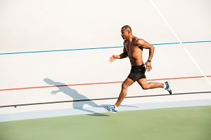 Full length portrait of a strong half naked sportsman running