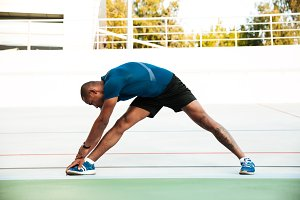 Full length portrait of a motivated sportsman doing stretching